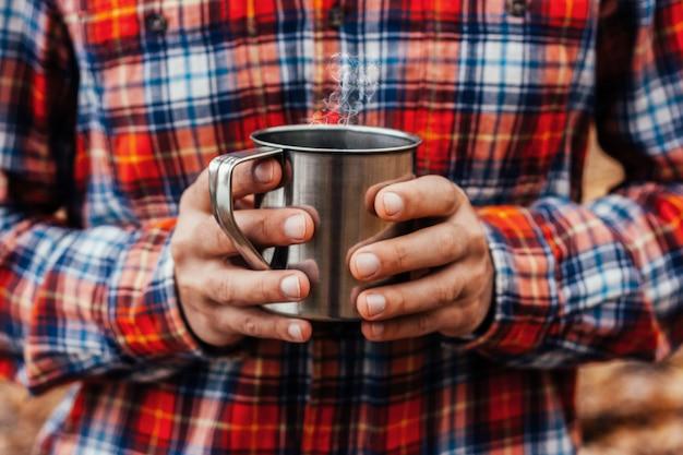 Copo de aço com uma bebida quente nas mãos do homem no parque outono