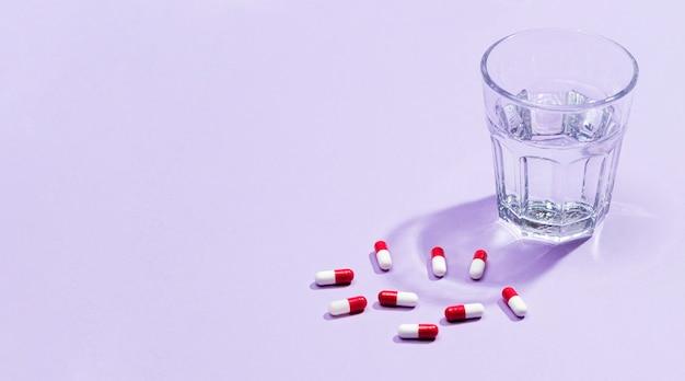 Copo de água ao lado de pílulas