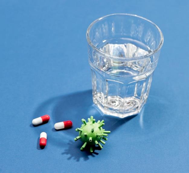 Copo de água com comprimidos ao lado de vírus
