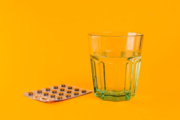 Copo de água com comprimidos em cima da mesa