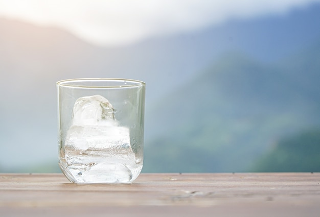 Copo de água com gelo na mesa de madeira no fundo desfocado