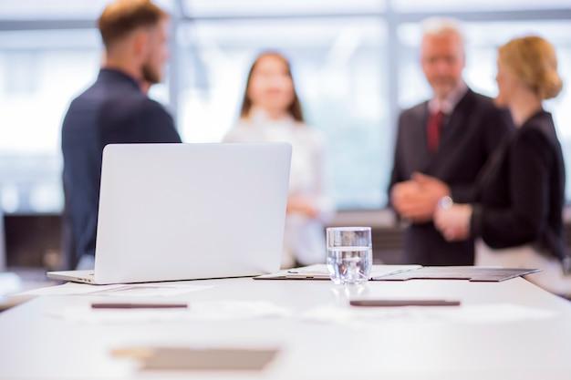 Copo de água com laptop na mesa na frente de empresários no fundo