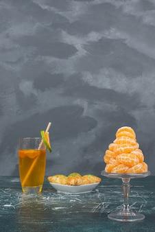 Copo de água com limão com prato de confeitaria e fatias de tangerina.