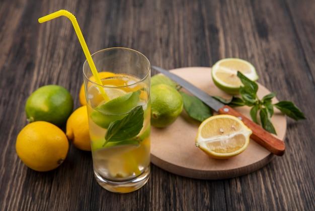 Copo de água com limão e rodelas de hortelã com canudo amarelo em fundo de madeira.