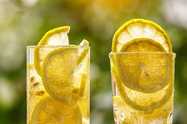 Copo de água com limão no jardim ensolarado. vista de close up.