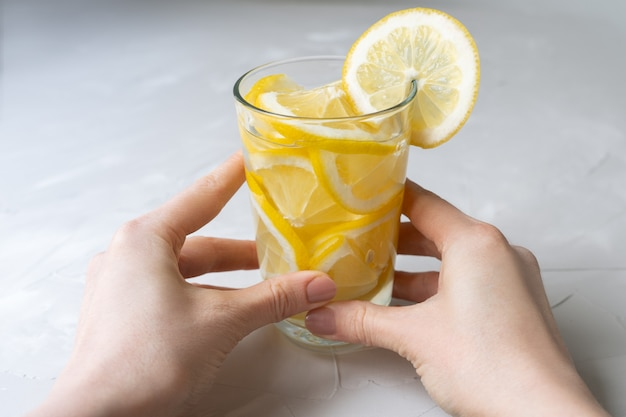 Copo de água com limão. uma dose de choque de vitamina c para tratar vírus. combate ao coronovírus com uma grande dose de vitamina c. as mãos seguram um copo com coquetel de limão