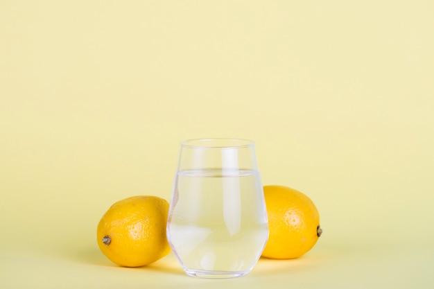 Copo de água com limões e fundo amarelo