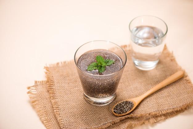 Copo de água com um copo de sementes de chia saudáveis e uma colher. espaço do texto.