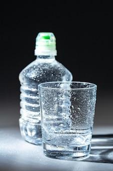 Copo de água com uma garrafa na mesa