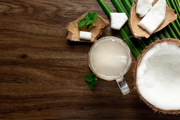 Copo de água de coco colocado sobre fundo escuro de madeira Foto gratuita