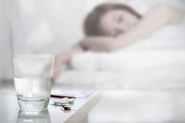 Copo de água e comprimidos com sofrimento mulher doente na cama.