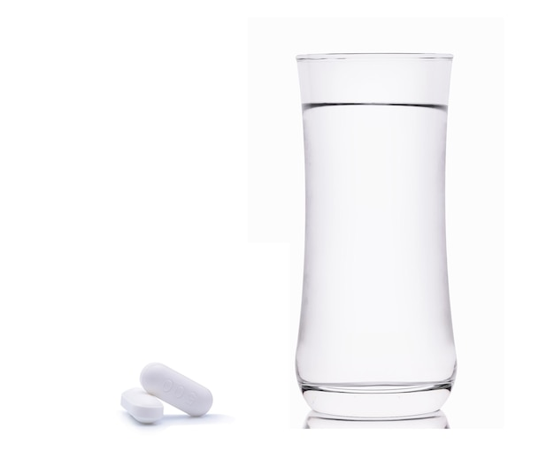 Copo de água e comprimidos isolados no branco