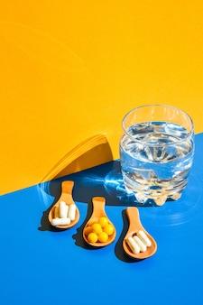Copo de água e comprimidos na colher de pau em fundo azul e amarelo com luz forte e sombras