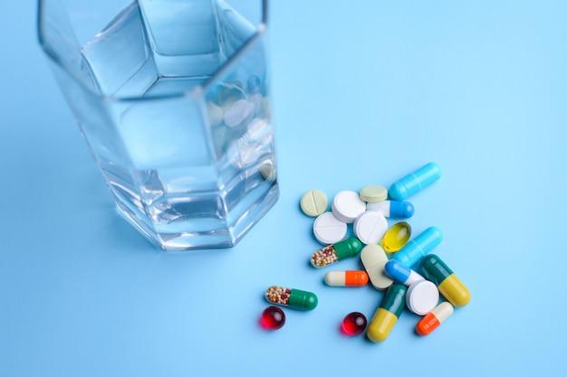 Copo de água e comprimidos na parede azul