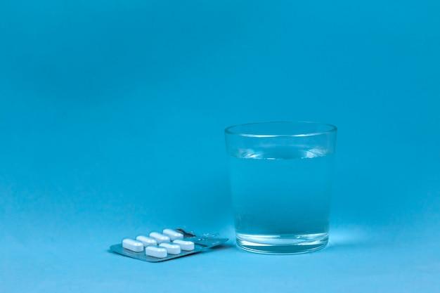Copo de água e comprimidos sobre fundo azul