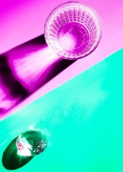 Copo de água e cristal com sombra brilhante no fundo dual