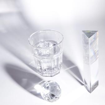 Copo de água e diamante de cristal e prisma com sombra escura sobre fundo branco