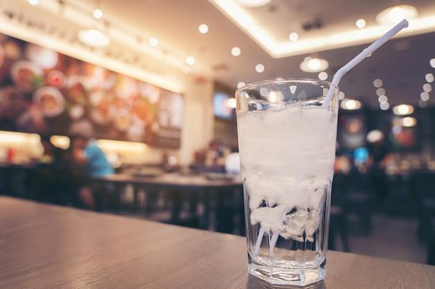 Copo de água gelada na mesa de madeira e luz turva no fundo do restaurante