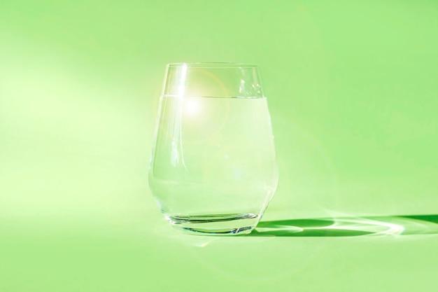 Copo de água limpa e fresca sobre fundo verde. água de nascente ecologicamente pura. desintoxicação, energia da água parada.
