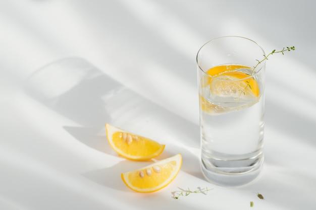Copo de água mineral com gás limpa com gelo e limão em um fundo branco com luz do sol. ilumine com sombras duras e brilho do vidro. café da manhã, bebida fresca da manhã