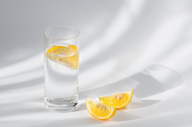 Copo de água mineral com gás limpa com gelo e limão em uma parede branca com luz do sol. ilumine com sombras duras e brilho do vidro. café da manhã, bebida fresca da manhã