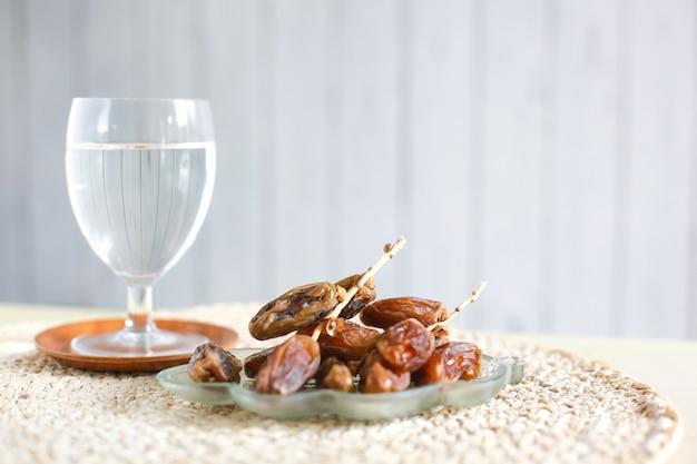 Copo de água mineral e tâmaras na mesa