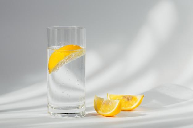 Copo de água mineral limpa com gás com gelo e limão em uma superfície branca com luz do sol