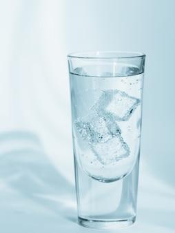 Copo de água mineral limpa com gás com gelo em uma parede azul clara