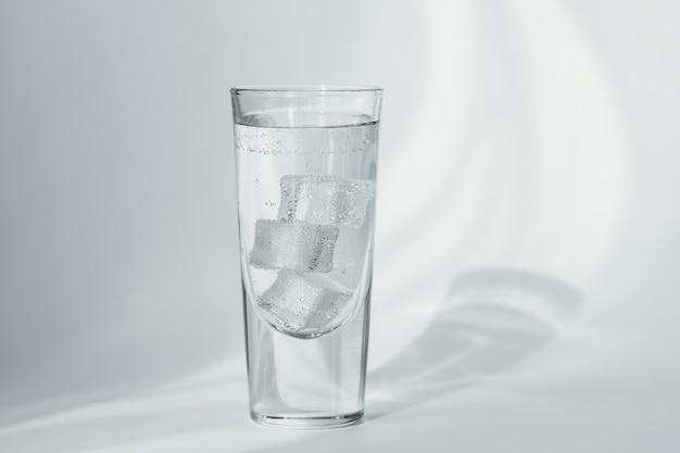Copo de água mineral limpa com gás com gelo em uma parede branca
