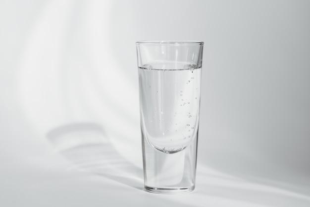 Copo de água mineral limpa com gás em um fundo branco