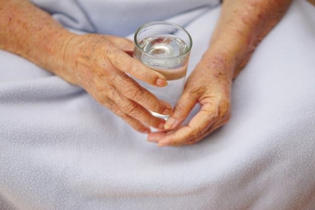 Copo de água na mão de um idoso