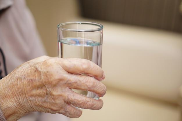 Copo de água na mão de uma senhora idosa idosa sênior ou asiática. saúde, amor, carinho, incentivo e empatia.