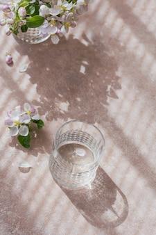 Copo de água na mesa com galho de macieira em flor em um copo