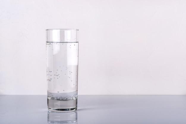 Copo de água no fundo branco. fechar-se.