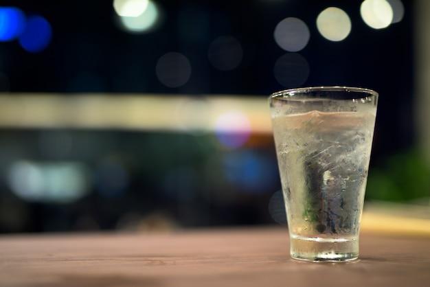 Copo de água potável na mesa de madeira à noite