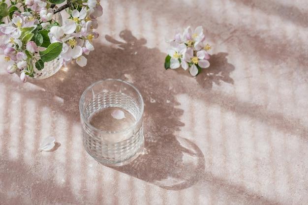 Copo de água pura em cima da mesa com um galho de macieira em flor