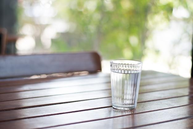 Copo de água pura em uma velha mesa de madeira em uma cafeteria com um verde