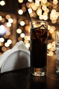 Copo de álcool com gelo no fundo manchado com círculo bokeh