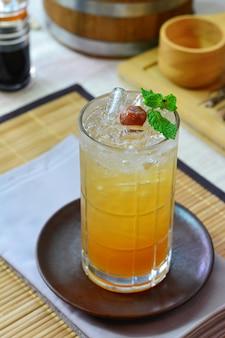 Copo de ameixa chinesa em copo redondo de vidro, napery e esteira de placa de bambu