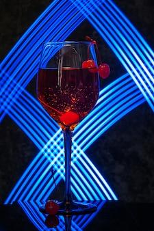 Copo de aperol spritz cocktail com cereja no escuro
