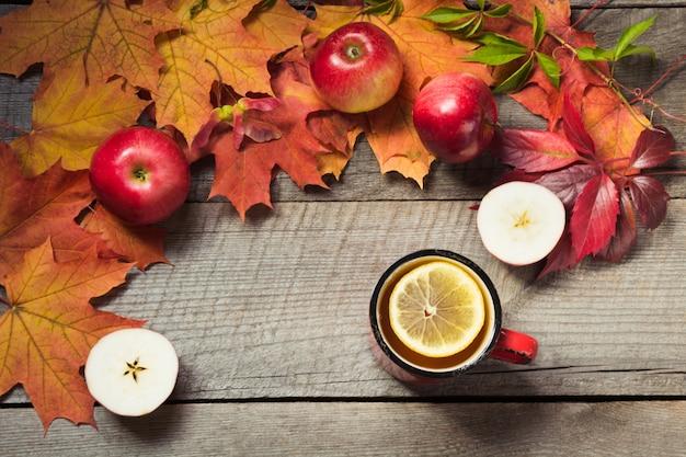 Copo de aquecimento do chá, decoração das folhas de outono, maçãs na placa de madeira. queda ainda vida. vista do topo.