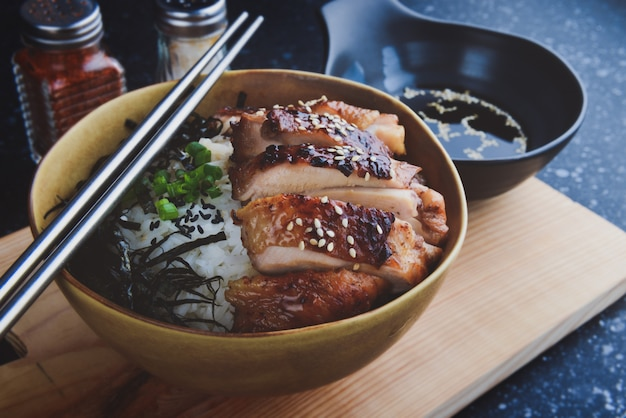 Copo de arroz com frango grelhado em estilo japonês.