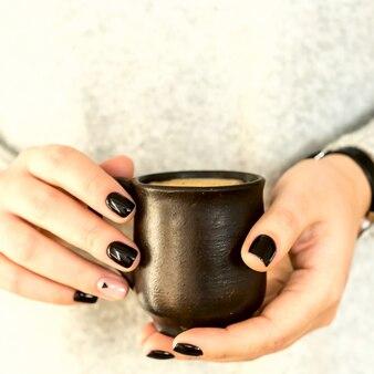 Copo de barro com café nas mãos de uma menina com uma manicure minimalista preto