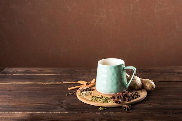 Copo de barro em uma placa de madeira sobre um fundo escuro. uma xícara de chá masala. especiarias cravo, erva-doce, canela, cardamomo, leite.
