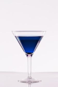 Copo de bebida alcoólica azul em uma parede branca