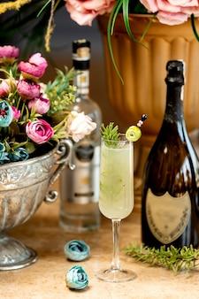 Copo de bebida alcoólica e um vaso de flores