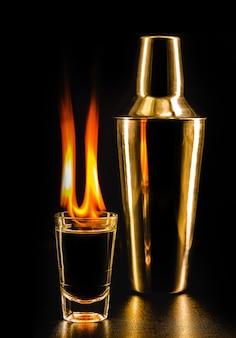 Copo de bebida alcoólica em chamas, vodka ou licor em chamas, superfície preta