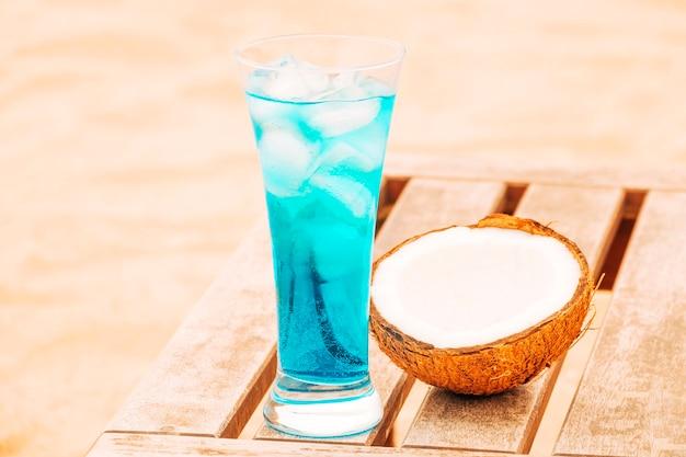 Copo de bebida azul fresco e coco rachado na mesa de madeira