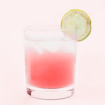 Copo de bebida cocktail com uma fatia de limão contra um fundo rosa