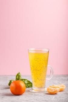 Copo de bebida colorida de laranja com tangerina com sementes de manjericão em um fundo cinza e rosa